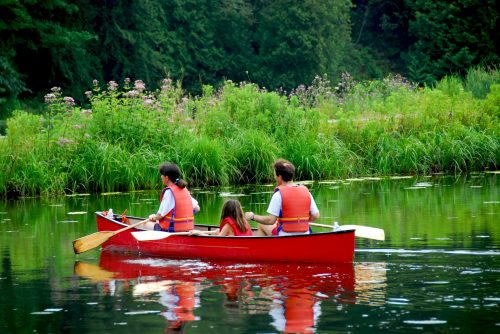 Family of three canoing on a calm river