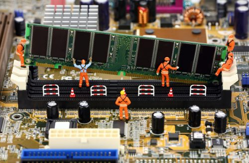 Miniature construction workers installing RAM memory on a computer motherboard.